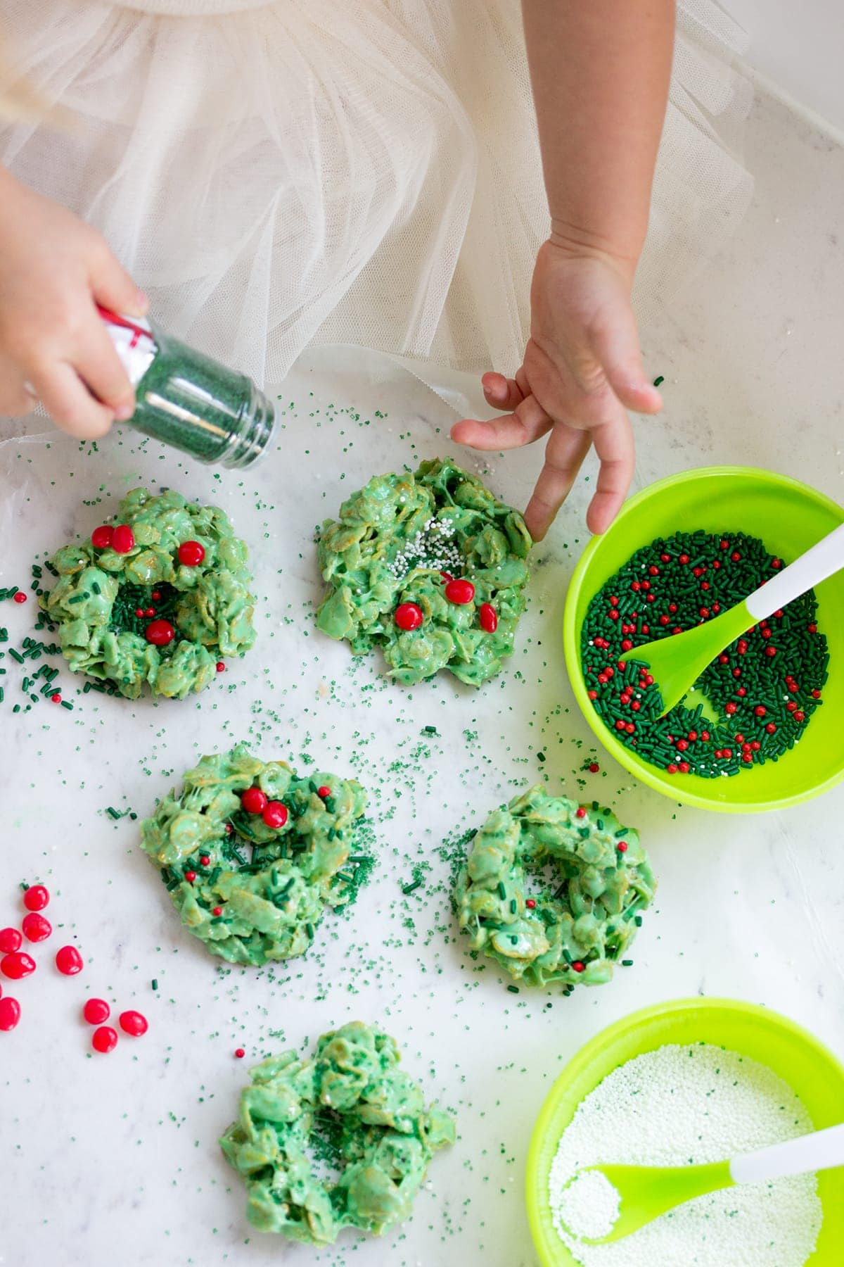 Classic Christmas Wreath Cookies, also known as holly wreath cookies, made with corn flakes and cinnamon candies are perfect for making with kids and leaving out for Santa on Christmas Eve.